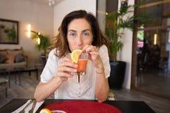 Kobieta pije marznącego truskawkowego margarita i patrzeć Zdjęcia Stock