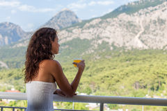 Kobieta pije sok pomarańczowego na hotelowym balkonie obrazy stock