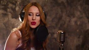 Kobieta piosenkarz nagrywa piosenkę w muzycznym studiu, wolnym zbiory