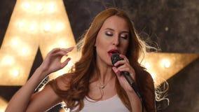 Kobieta piosenkarz z czerwonymi wargami i mikrofonem błyszczy, zbiory