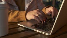 Kobieta pisać na maszynie na klawiaturze notatnik w słonecznym dniu, w górę widoku palce zdjęcie wideo