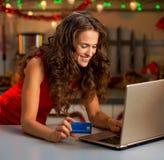 Kobieta pisać na maszynie na laptopie w Bożenarodzeniowej kuchni z kredytową kartą Fotografia Royalty Free