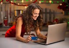 Kobieta pisać na maszynie na laptopie w Bożenarodzeniowej kuchni z kredytową kartą Zdjęcia Royalty Free