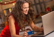 Kobieta pisać na maszynie na laptopie w Bożenarodzeniowej kuchni z kredytową kartą Obraz Stock