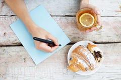 Kobieta pisze artykule i pije gorącej herbaty Odgórny widok Conc Zdjęcia Royalty Free