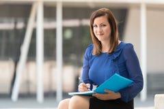 Kobieta pisze dalej w błękitnej książce fotografia stock