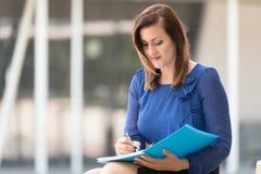 Kobieta pisze dalej w błękitnej książce zdjęcie stock