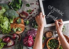 Kobieta pisze kreda na blackboard, żywność organiczna, zdrowa świeża sałatka, avocado, zielenie, arugula obraz stock