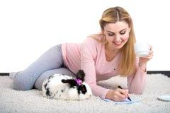 Kobieta pisze liście w romantycznej domowej atmosferze, kłama na dywanie z królikiem obrazy royalty free
