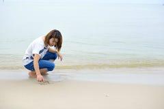 Kobieta pisze na piasek plaży zdjęcie royalty free