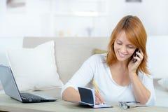 Kobieta pisze puszka spotkaniu w dzienniczku z telefonem komórkowym obrazy stock