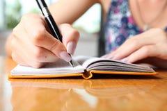 Kobieta pisze w notatniku obraz stock