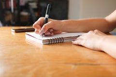 Kobieta pisze w notatniku fotografia stock