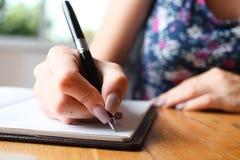 Kobieta pisze w notatniku obrazy royalty free