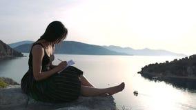 Kobieta pisze w notesie siedzÄ…cym wysoko na skale nad morzem w zwolnionym tempie zbiory