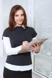 Kobieta pisze w skoroszytowej pozyci przy okno zdjęcie stock