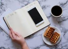 Kobieta planuje dzie?, kawa, gofry, marmurowy t?o, smartphone obraz stock