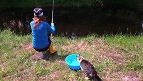 Kobieta połów na jeziornej brzeg i kota cath ryba od wiadro wody zbiory
