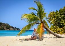 Kobieta pod drzewkiem palmowym na plaży Zdjęcie Royalty Free