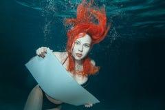 Kobieta pod wodą z znakiem w jego ręki Obrazy Stock