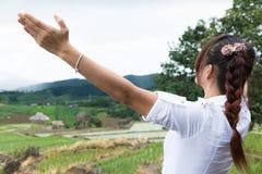 Kobieta podnosi jej rękę z szczęściem przy zielonym ryżu polem na terra fotografia royalty free