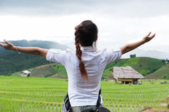 Kobieta podnosi jej rękę z szczęściem przy zielonym ryżu polem na terra zdjęcia stock