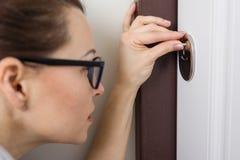 Kobieta podpatruje przy keyhole w dzwi wejściowy, w domu obrazy stock