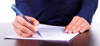Kobieta podpisuje kontrakt na stole, odosobniony nadmierny biel Obrazy Stock