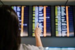 Kobieta podróżniczy sprawdza lot odjazdy wsiada przy airpor zdjęcia stock