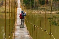 Kobieta podr??nik bierze obrazek od zawieszenie mostu nad wiosny rzek? zdjęcie royalty free