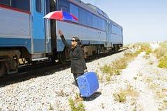 Kobieta podróżnik przy przelotnym pociągiem Zdjęcie Royalty Free