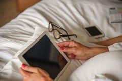 Kobieta podróżnik używa pastylka komputer w łóżku w pokoju hotelowym obrazy stock