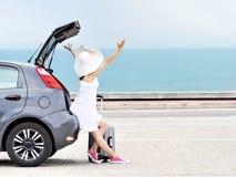 Kobieta podróżnik z nastroszonymi rękami na hatchback samochodzie na plaży zdjęcia stock