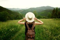 Kobieta podróżnik z plecaka mienia kapeluszem i patrzeć zadziwiający Obraz Royalty Free