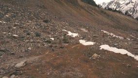 Kobieta podróżnik z psim bieg wokoło w górach, lodowiec, strzał od powietrza zdjęcie wideo