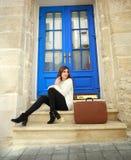 Kobieta podróżnik z walizki siedzieć marzycielski przy jej domem Obraz Royalty Free