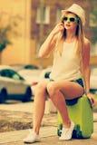 Kobieta podróżnik siedzi na walizki czekaniu dla samochodu Obraz Royalty Free