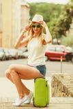 Kobieta podróżnik siedzi na walizki czekaniu dla samochodu Zdjęcie Stock