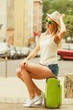 Kobieta podróżnik siedzi na walizki czekaniu dla samochodu Zdjęcie Royalty Free