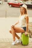 Kobieta podróżnik siedzi na walizki czekaniu dla samochodu Fotografia Stock