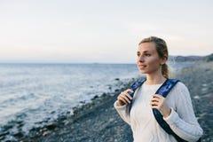 Kobieta podróżnik w biel ubraniowej pozyci na brzeg i spojrzeniach przy morzem Obraz Stock