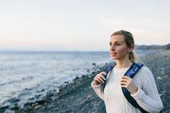 Kobieta podróżnik w biel ubraniowej pozyci na brzeg i spojrzeniach przy morzem Fotografia Stock