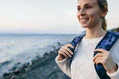 Kobieta podróżnik w biel ubraniowej pozyci na brzeg i spojrzeniach przy morzem Zdjęcie Stock
