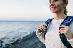 Kobieta podróżnik w biel ubraniowej pozyci na brzeg i spojrzeniach przy morzem Zdjęcie Royalty Free