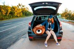 Kobieta podróżnika obsiadanie na hatchback samochodzie Zdjęcie Stock