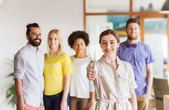 Kobieta pokazuje aprobaty nad kreatywnie biuro drużyną zdjęcie stock