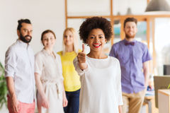 Kobieta pokazuje aprobaty nad kreatywnie biuro drużyną obraz stock