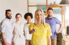 Kobieta pokazuje aprobaty nad kreatywnie biuro drużyną fotografia royalty free