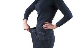 Kobieta pokazuje ciężar stratę być ubranym starych dużych spodnia Pojęcie ciężar strata Obrazy Royalty Free