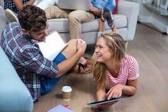 Kobieta pokazuje cyfrową pastylkę męski przyjaciel w domu Fotografia Stock